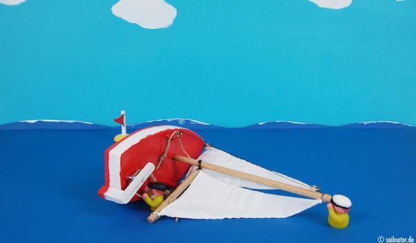 Das schwerere Crewmitglied schwimmt zur Mastspitze und verhindert, dass das Boot durchkentert! Das leichtere Crewmitglied löst alle Schoten.
