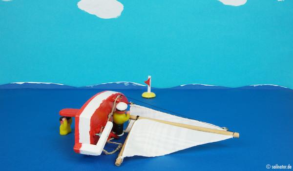 Das schwerere Crewmitglied kann jetzt die Mastspitze loslassen und klettert im Boot auf den Rand hoch, der aus dem Wasser ragt.