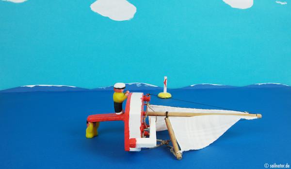 ... auf das Schwert mit dem Gesicht zum Boot. Er hält sich am Rand fest und balanciert das Boot aus.