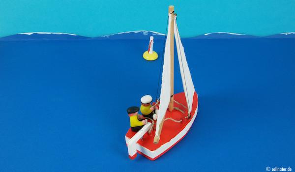 """""""Hol an die Schoten auf Amwindkurs!"""" Das Boot ist noch voller Wasser. Die Lenzventile müssen geöffnet werden und die beiden fahren an Land, um trockene Kleidung anzuziehen!"""